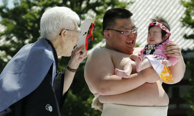 Zawodnicy sumo zmuszają do płaczu niemowlaki. Oto coroczny japoński festiwal nakizumo [ZDJĘCIA]