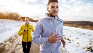 Kobieta z mężczyzną biegają zimą