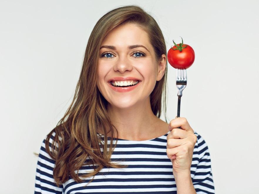 Kobieta trzyma pomidora na widelcu