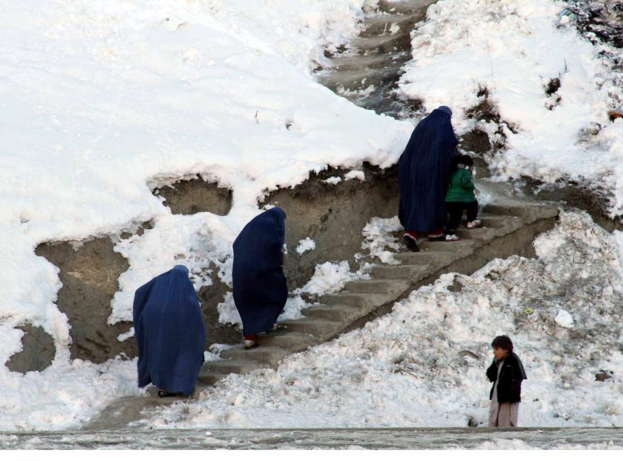 Kobiety w burkach wspinają się po oblodzonych schodach na wzgórze w okolicach Kabulu
