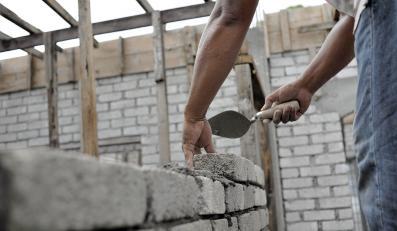 Murarz stawia ścianę z cegieł na budowie domu