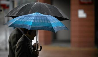 Przechodnie pod parasolami