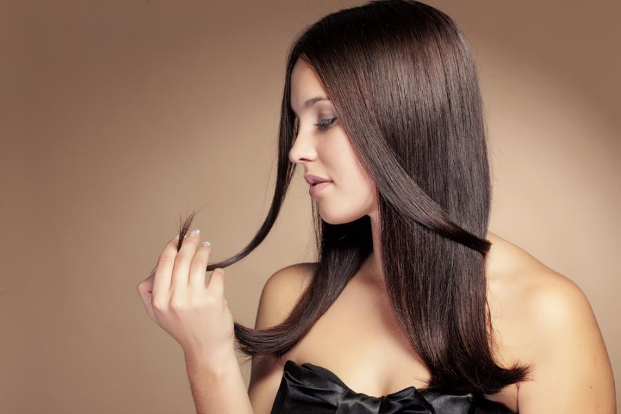 Kobieta oglądająca końcówki swoich włosów
