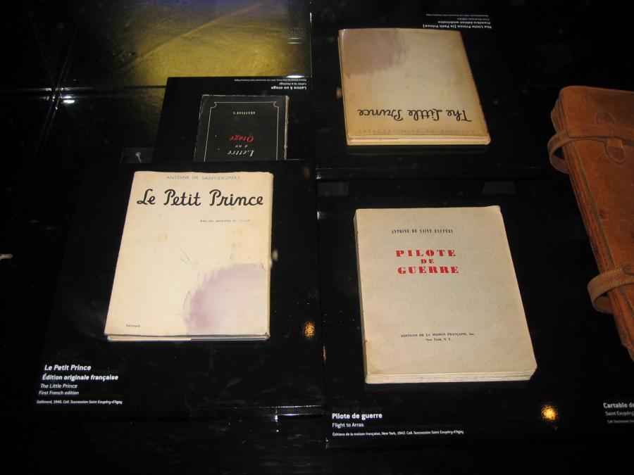 Dwa pierwsze wydania Małego Księcia (po lewej u dołu po francusku, po prawej u góry po angielsku) na stałej wystawie poświęconej Antoine de Saint-Exupéry'emu we francuskim Muzeum Lotnictwa i Astronautyki Le Bourget.