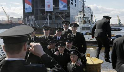 Rosyjska załoga na tle okrętu typu mistral