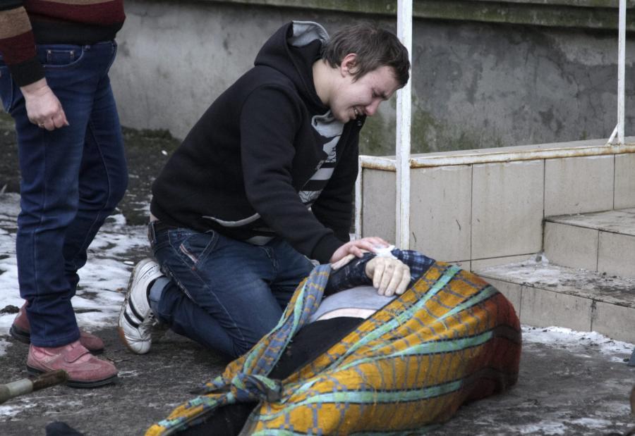 Mężczyzna rozpacza nad ciałem swojego dziadka, który zginął w ostrzale Doniecka