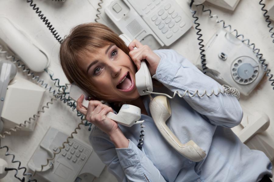 Młoda kobieta otoczona telefonami