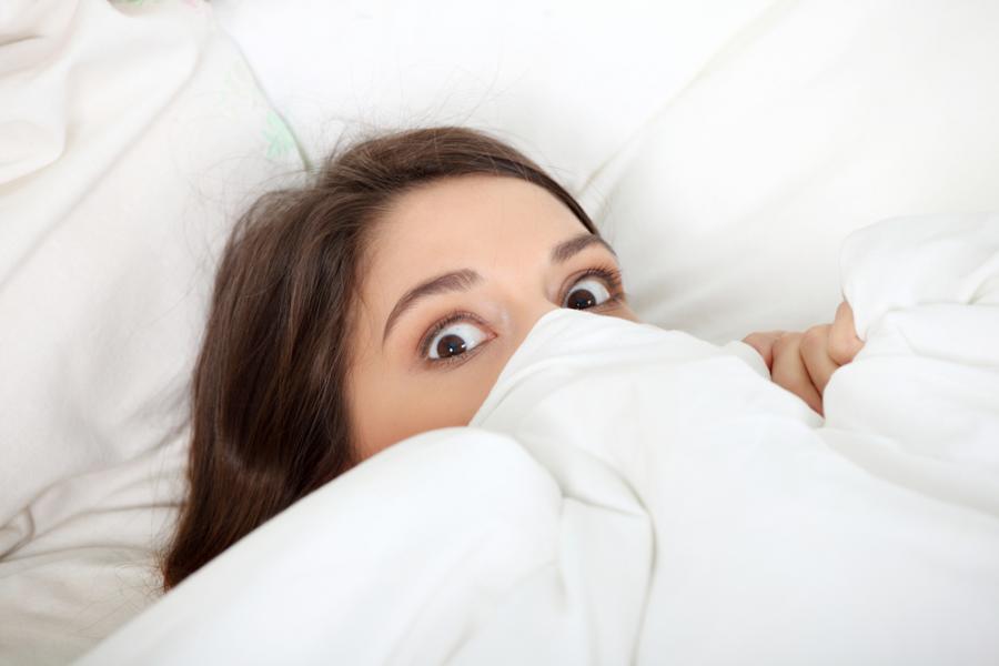 Przerażona kobieta w łóżku