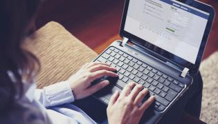 Kobieta przegląda Facebook w laptopie