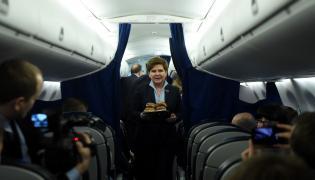 Premier Beata Szydło częstuje dziennikarzy pączkami na pokładzie samolotu