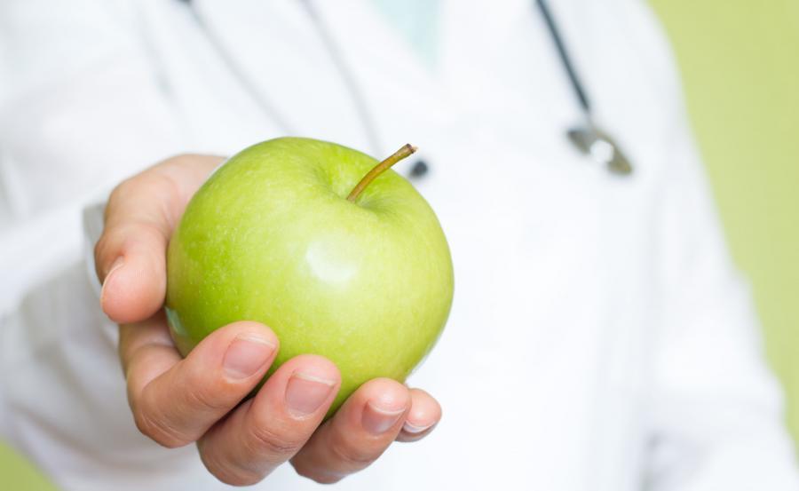 Lekarz trzyma jabłko