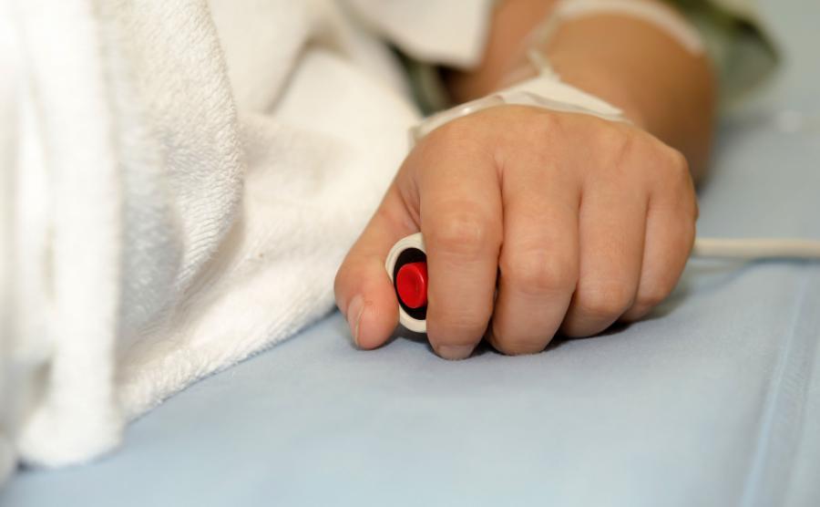 Chory w szpitalu trzyma przycisk do wezwania pomocy